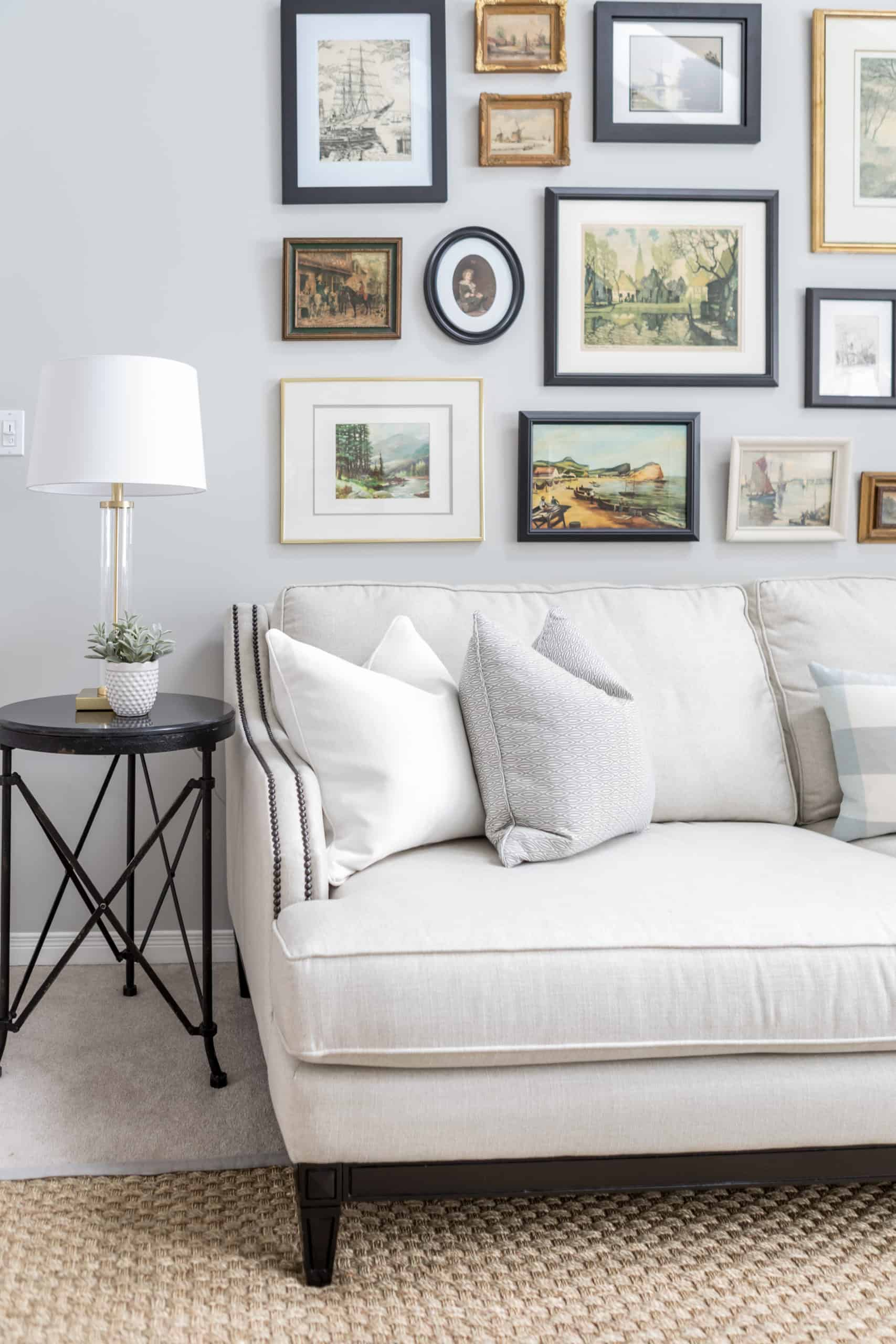 Many pictures above a white couch