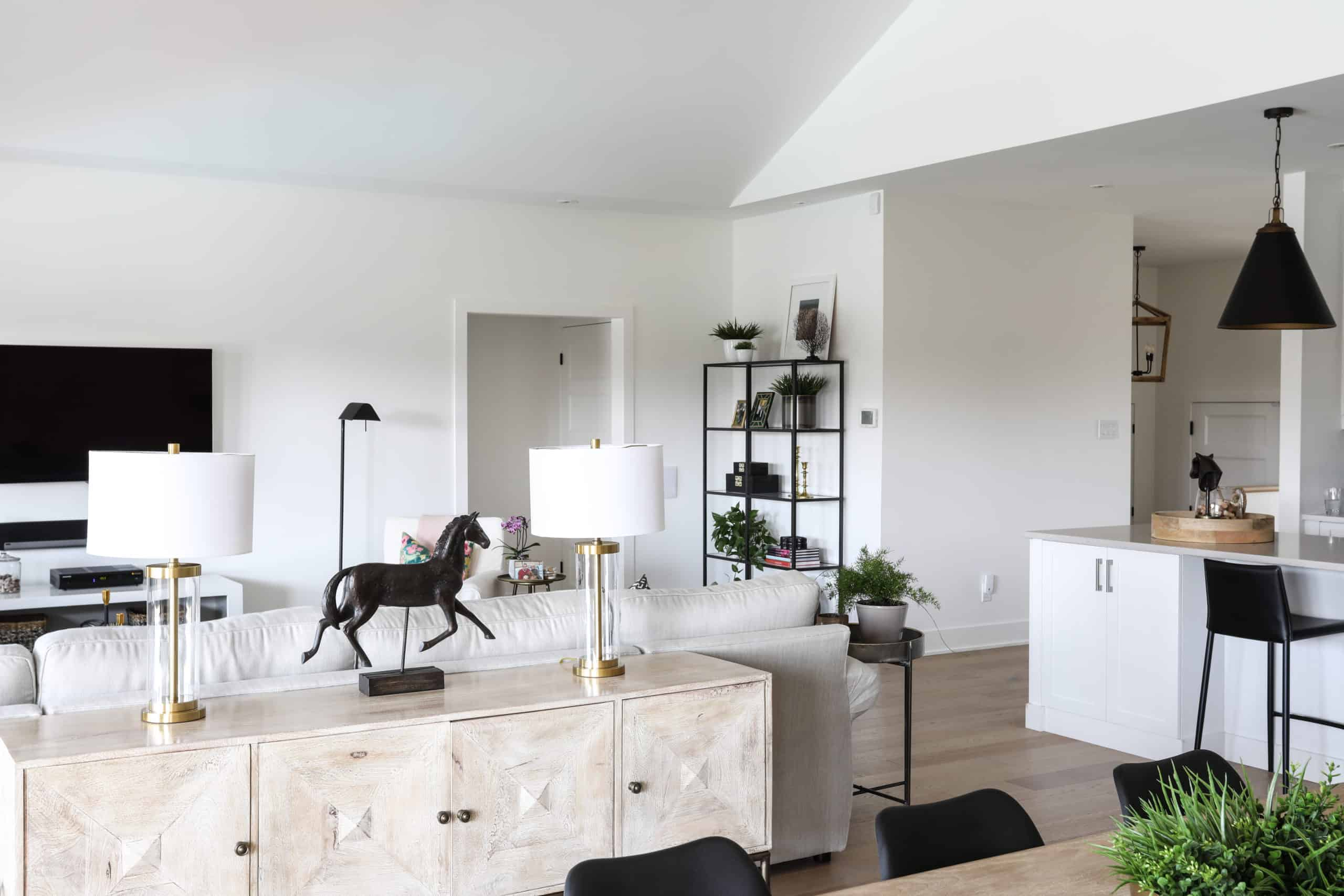 Black horse figure on a white, modern, short cupboard against a bright white couch