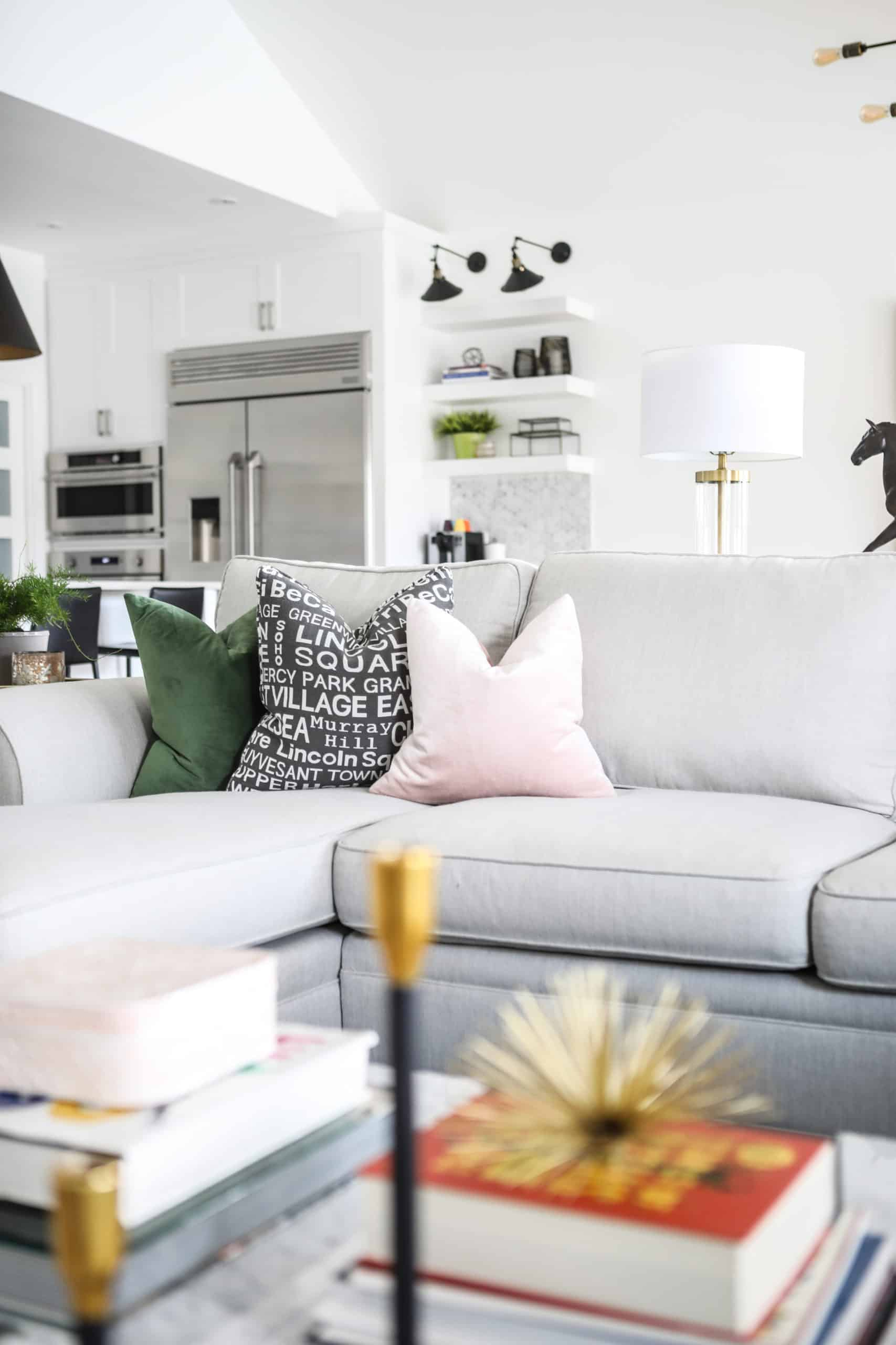 Pillows at the corner a a bright gray couch