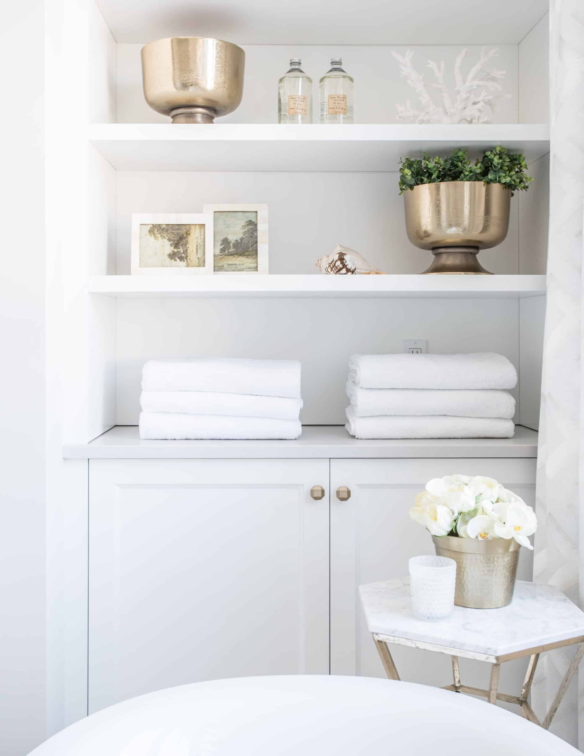 Bookshelf with white towels and decorations on it
