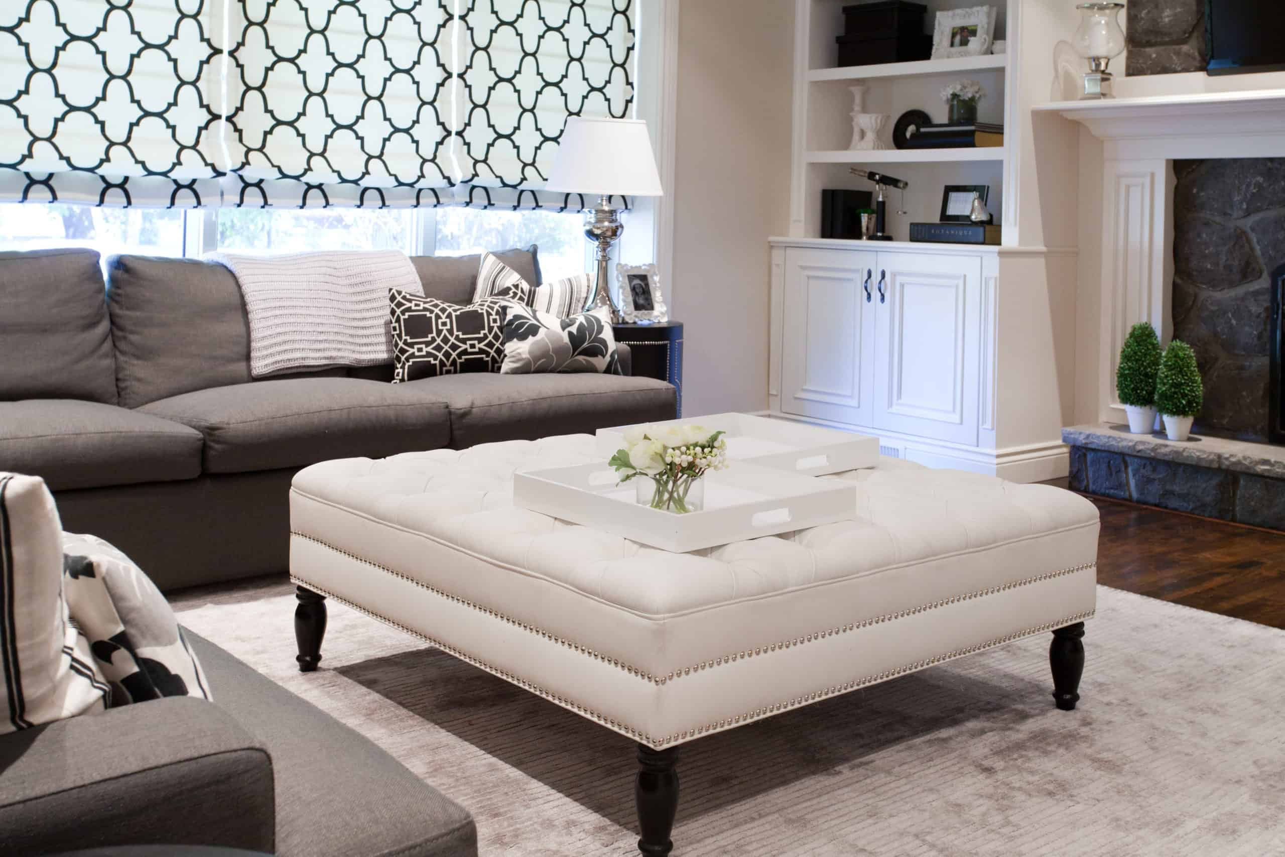 Large, modern living room with a focus on the white ottoman