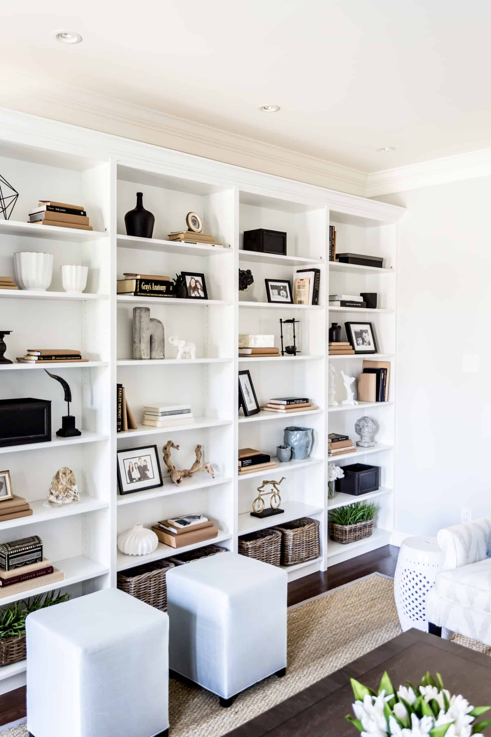 Massive bookcase covering large wall with an assortment of decorations on it