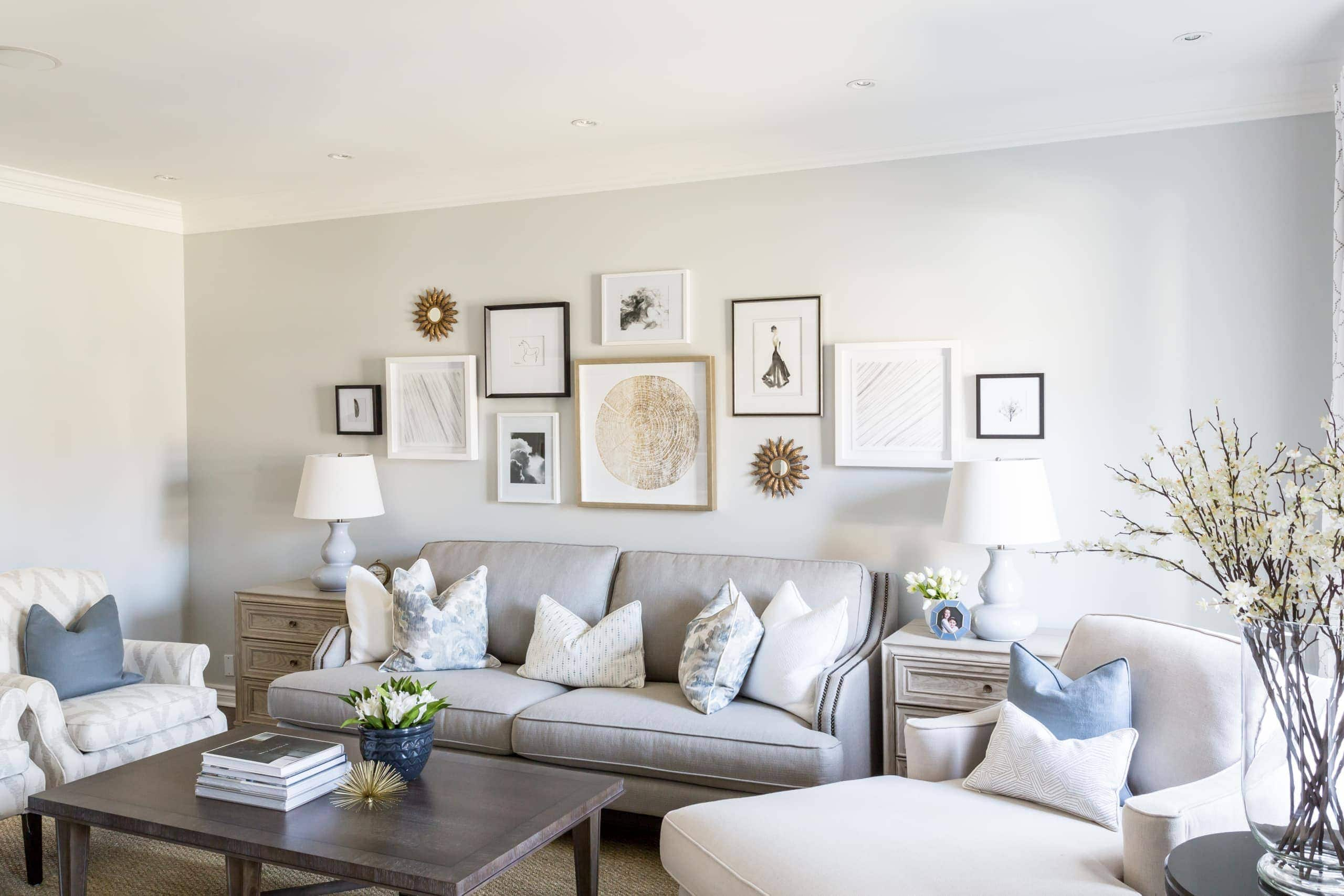 Gray couch with with eleven pictures above it