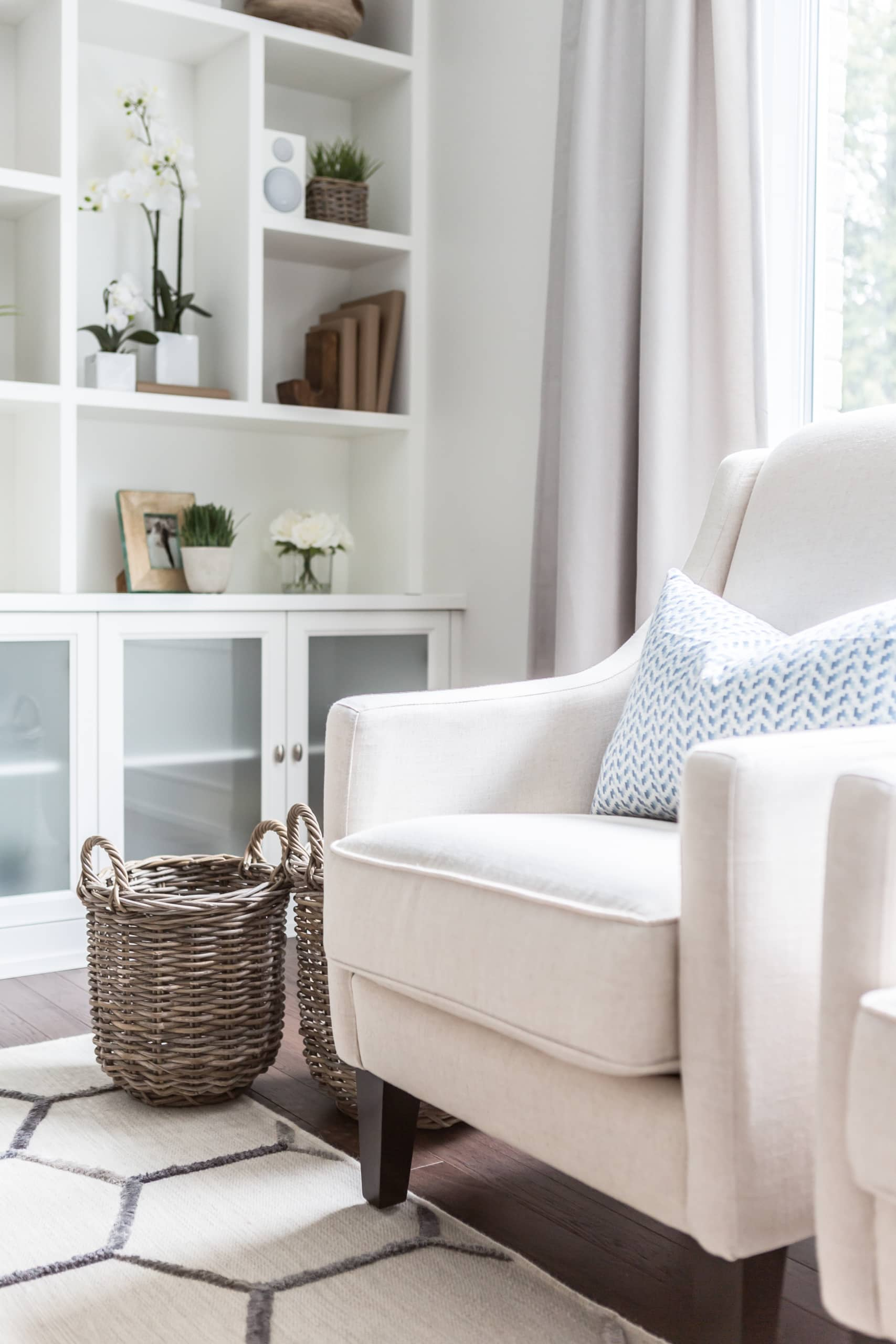 White chair with two baskets next to it
