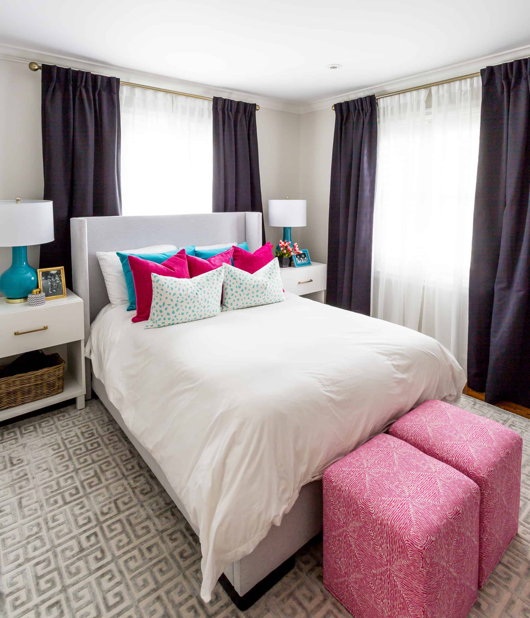 Array of white, blue, and pink pillows on a white bed