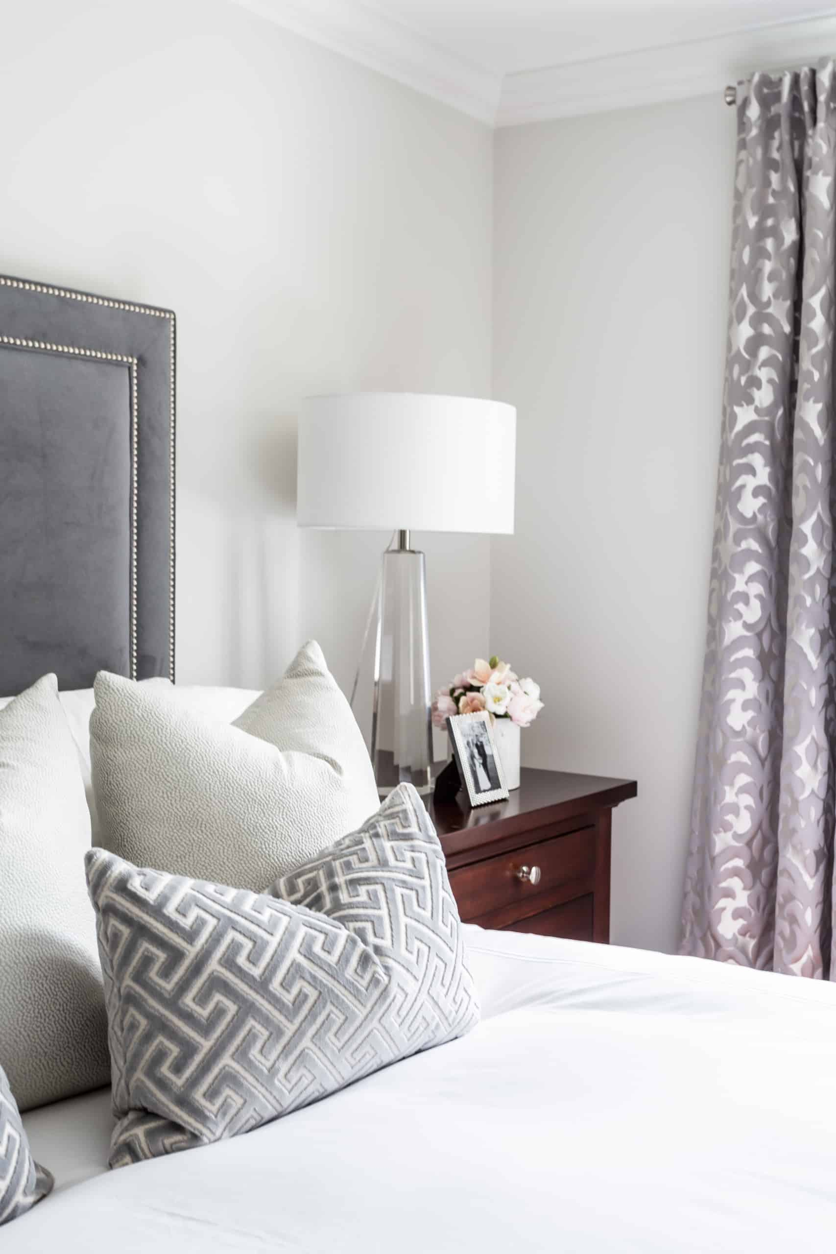 Array of white and gray pillows on a large white bed