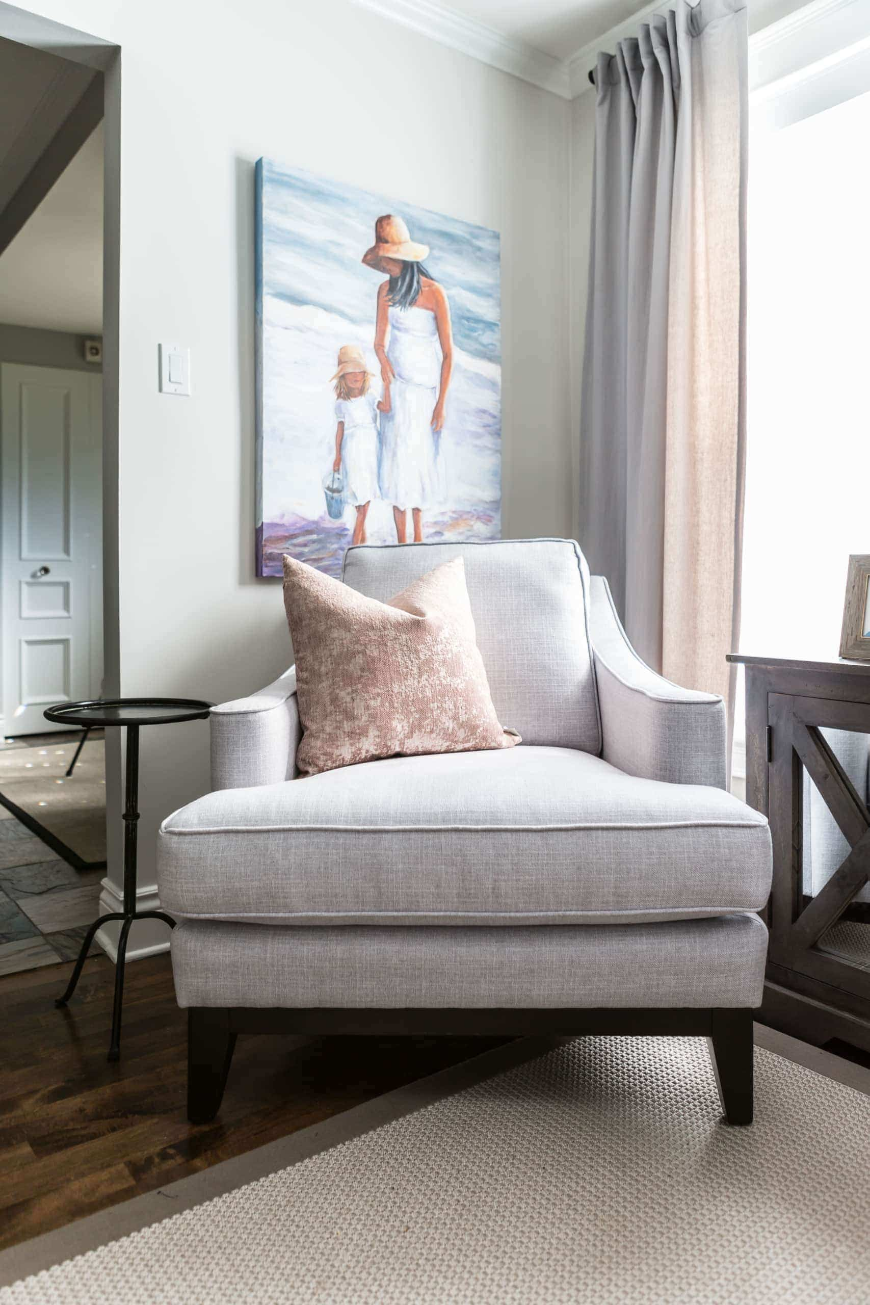 Gray chair with a pink pillow on it