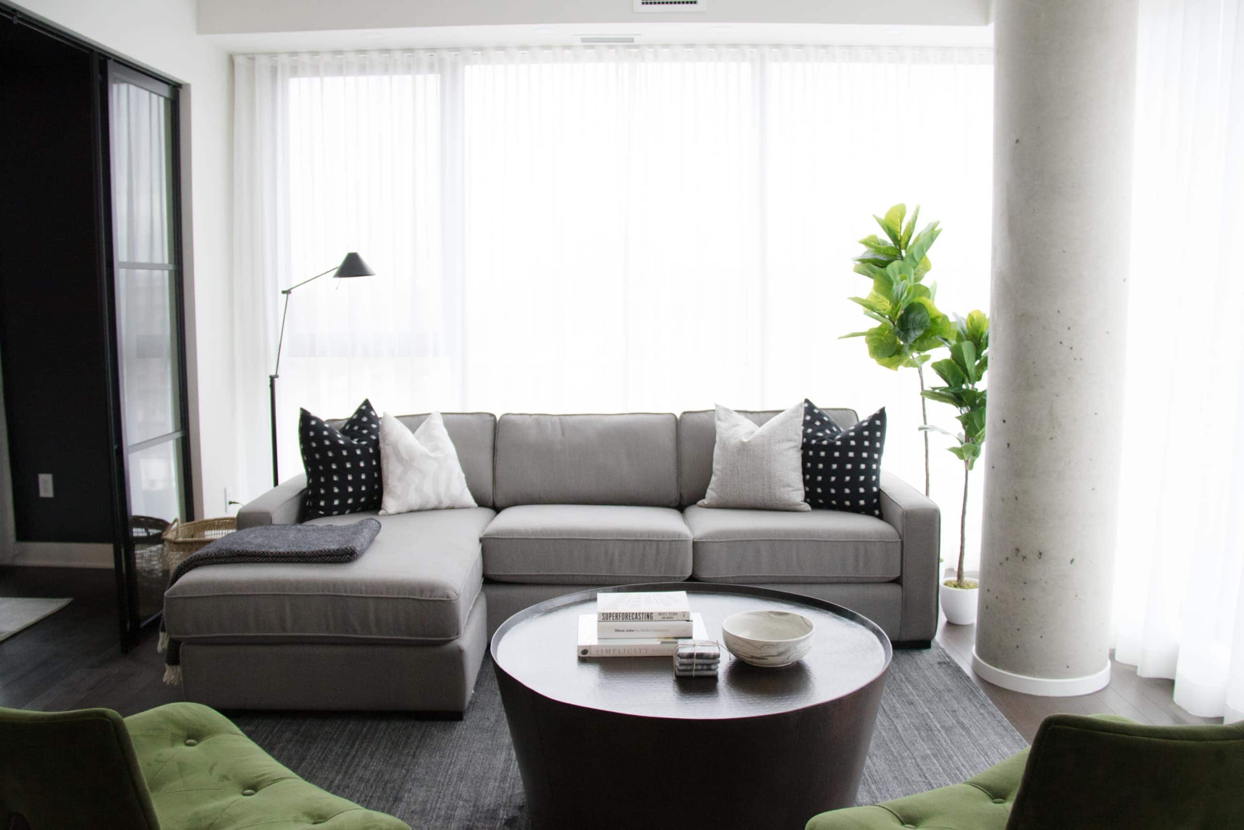 Modern living room with green chairs in the corners