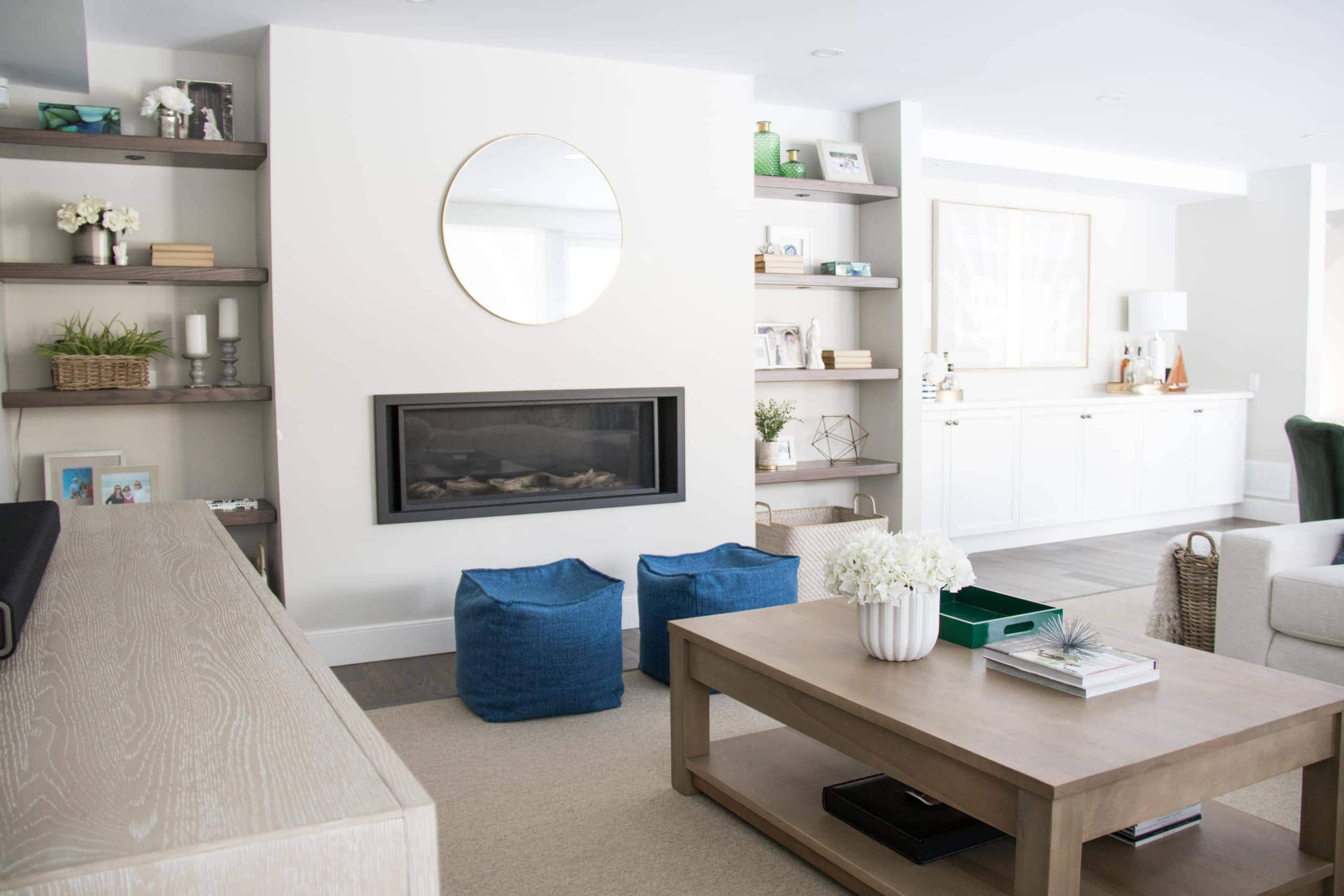 Bright living room containing blue seats in front of the fireplace