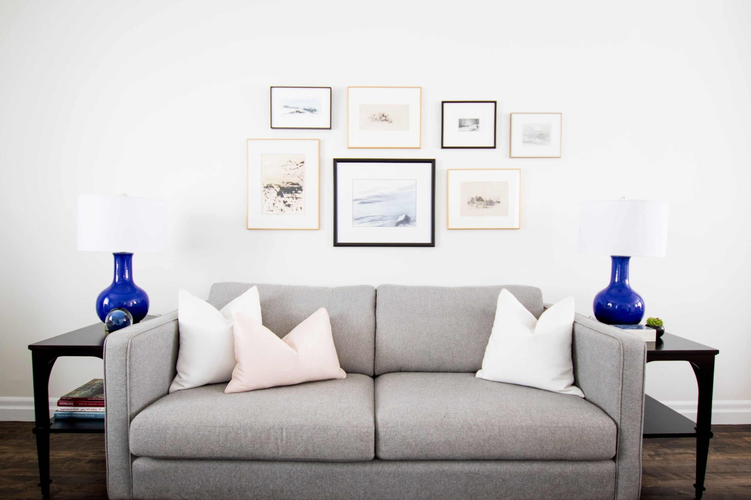 Gray couch with pictures above it inside living room