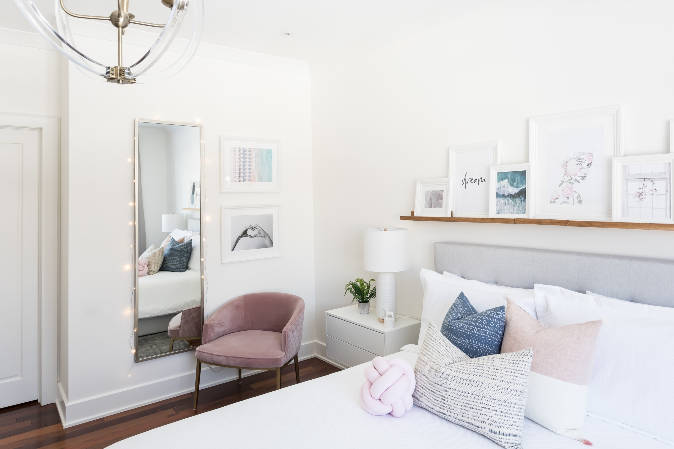 Large bed with pictures on a shelf above it in master bedroom