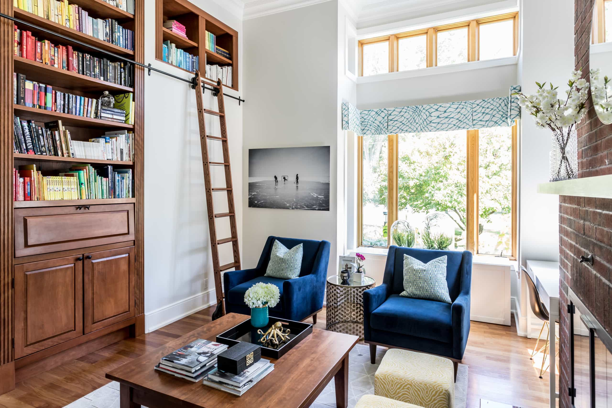 Tall living room with a ladder to reach the top bookshelf's