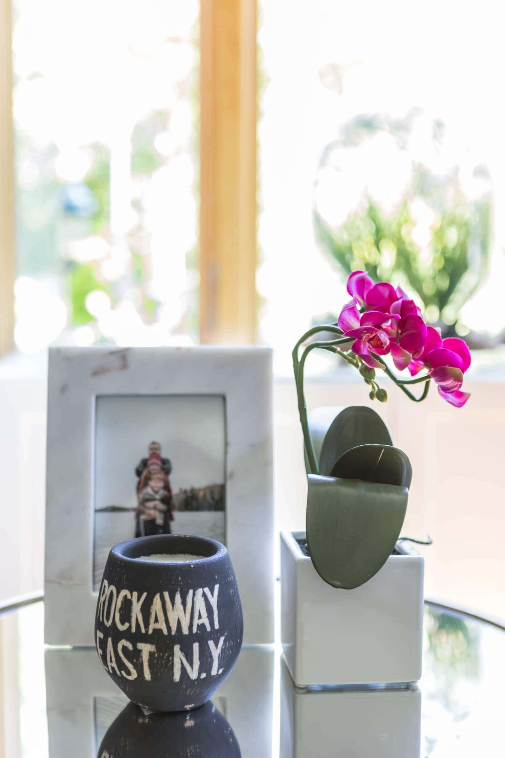 Pink flower on a table with a picture and a cup
