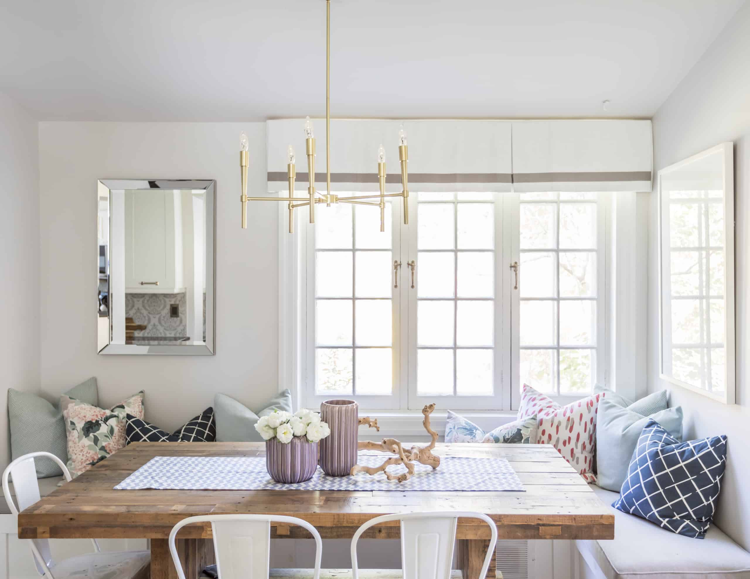 Long, wooden dining room table with a skinny chandelier