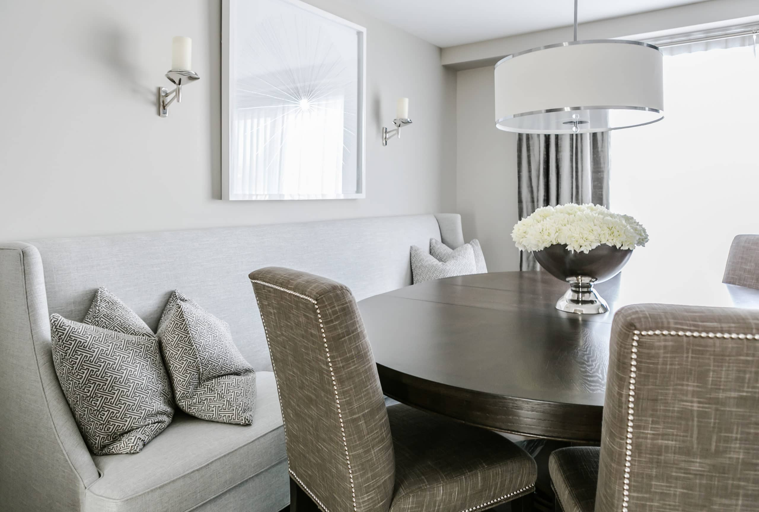 Modern dining room with a gray couch against the wall