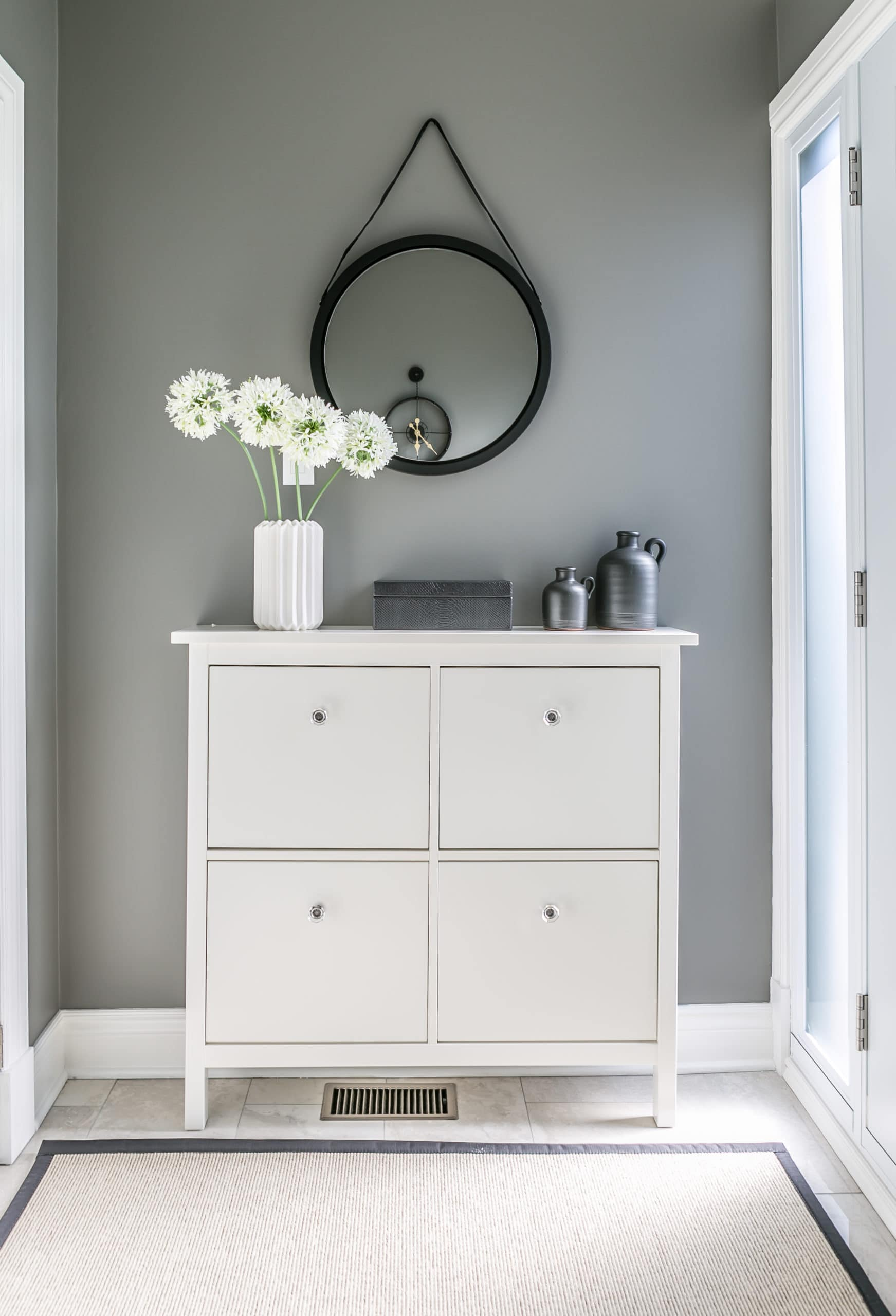 Beautiful white flowers on a small shelving unit at the end of a hallway