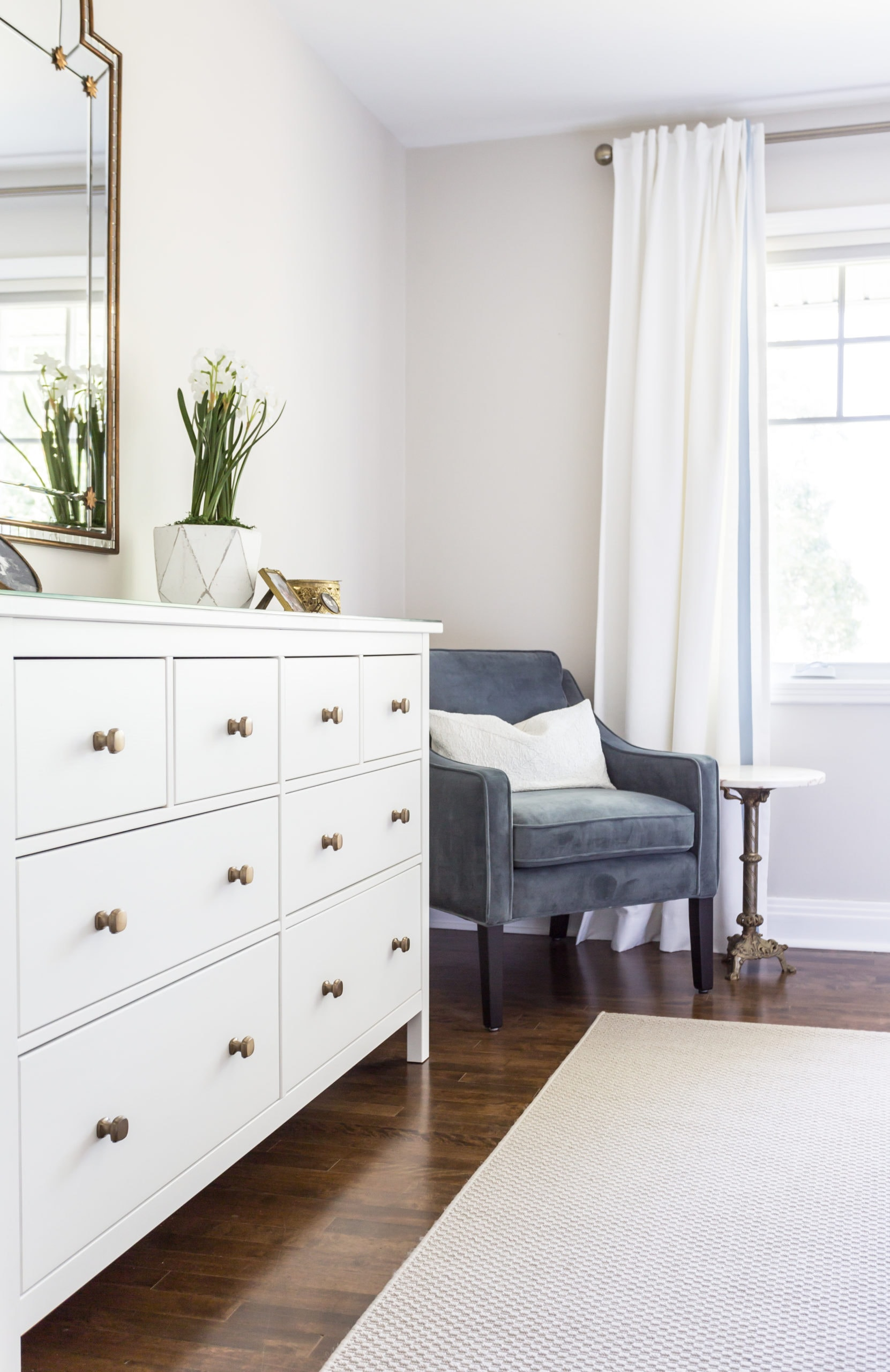 Large white dresser with a small blue comfy chair