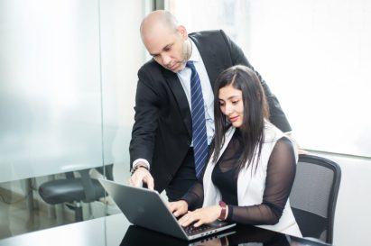 A BLH stock image of two accountants checking a computer. BLH can assist investors with the new Colombia tax reform.
