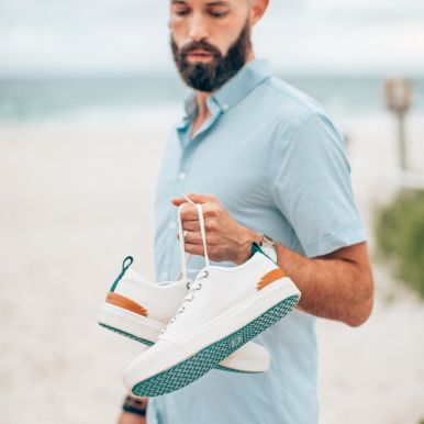 Michael Checkers holding TOMS sneakers on South Beach