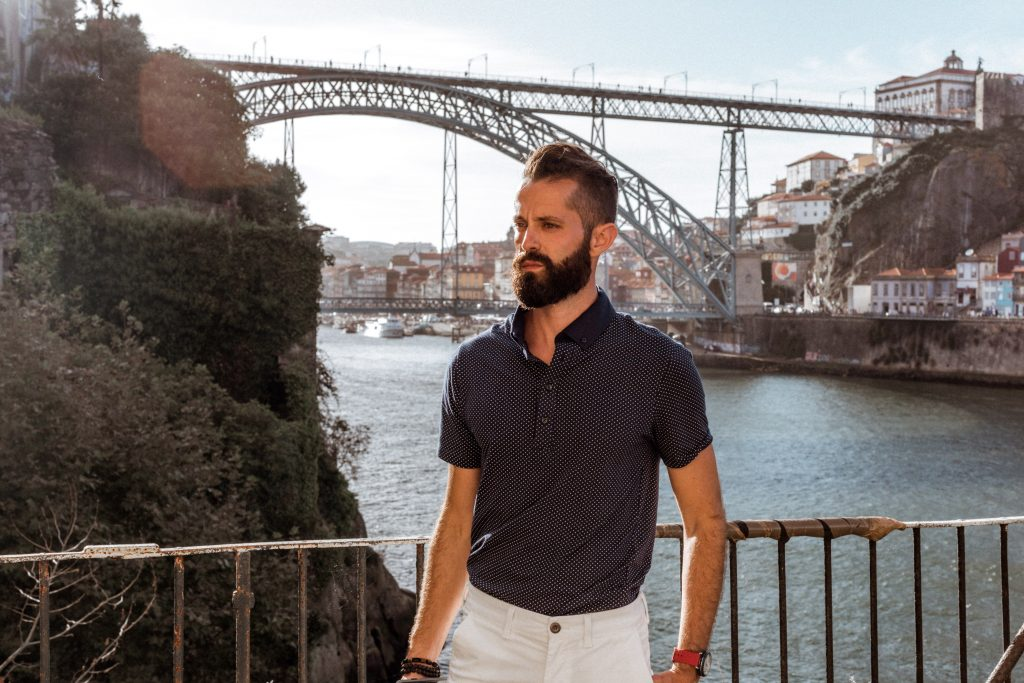 Michael Checkers men's fashion influencer standing in front of bridge in Porto Portugal wearing a blue polo shirt