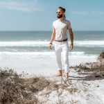 michael checkers men's fashion influencer wearing express white pants on a beach