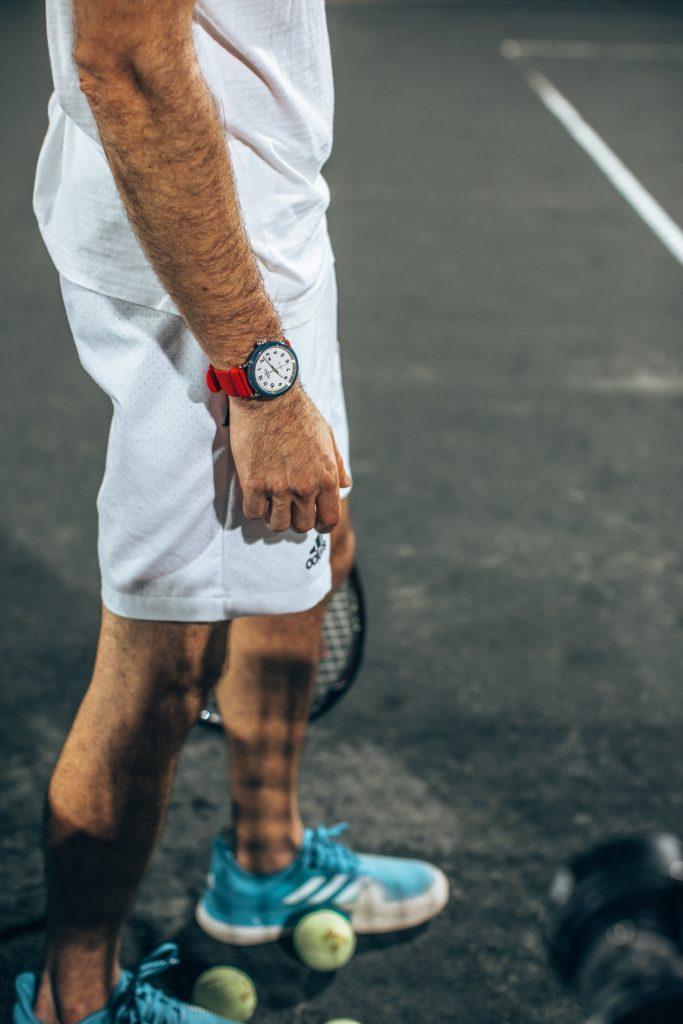 Michael Checkers wearing a Shinola Detrola Ace watch on a tennis court in Miami waist down