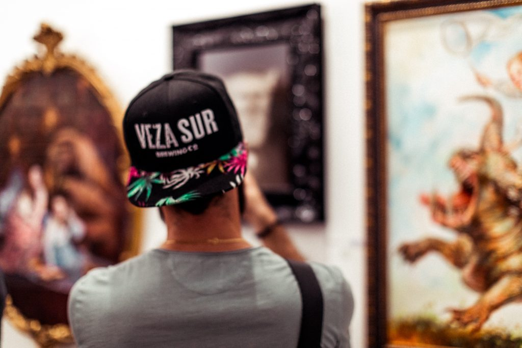 Michael Checkers wearing a Veza Sur hat taking a photo at SCOPE Miami Beach