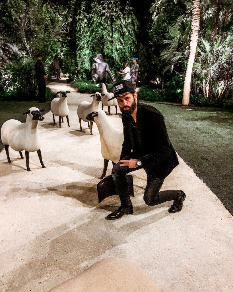 Michael Checkers wearing all black in Miami doing a streetwear pose at an art show