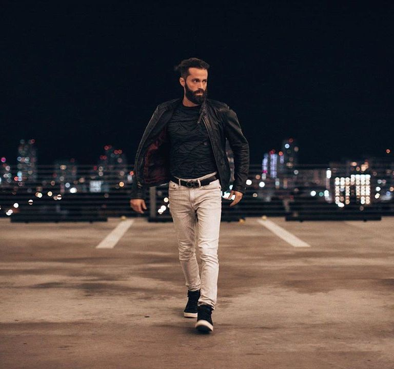 Michael Checkers wearing jeans and a leather jacket walking fast with city skyline in the background at night in Miami