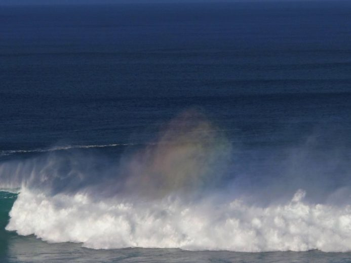 A wavebow is seen in the mist as waves crash onto shore at first morning light
