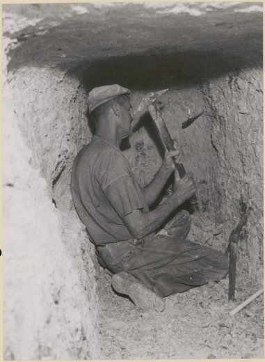 Opal miner, George Lowe chips away at the face of his opal mine, Lightning Ridge, 1953 by Bill Brindle
