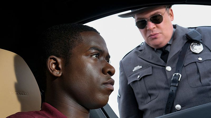 "Damson Idris sits in his car as a police officer (played by Glenn Fleshler) in the episode ""Replay"" in the rebooted Twilight Zone series."