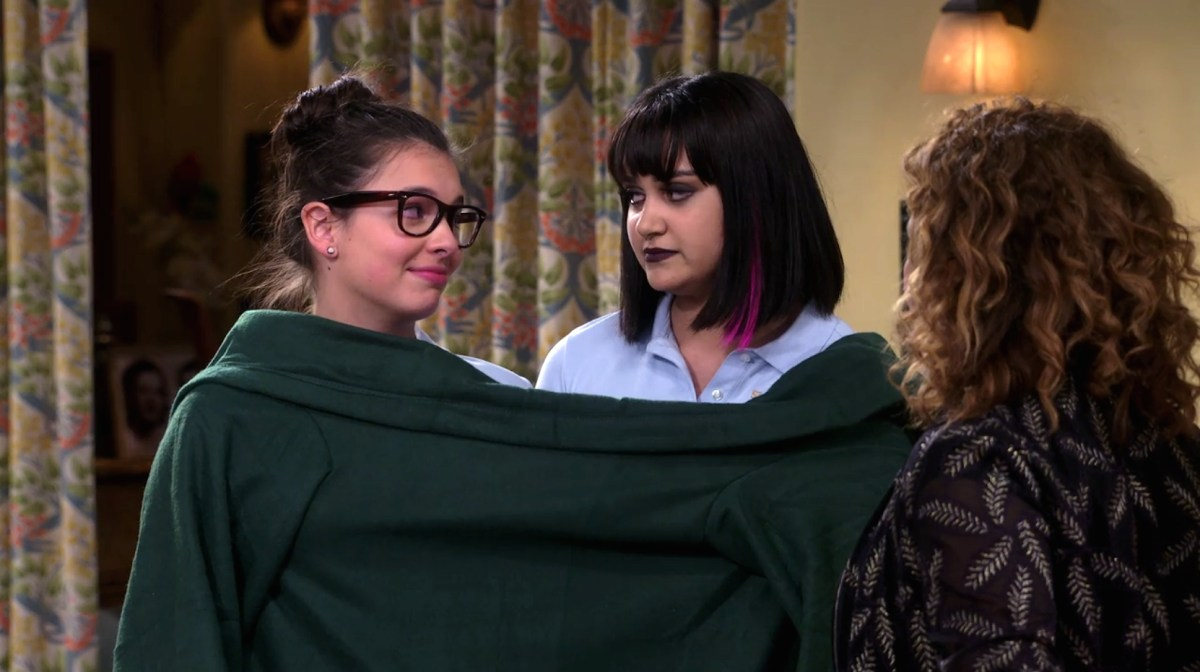 Elena (Isabella Gomez) and her friend Carmen (Ariela Barer) share a large robe to show how close they are.