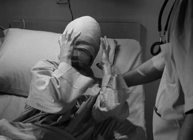 "Maxine Stuart sits in a hospital bed with bandages covering her head in the classic Twilight Zone episode ""Eye Of The Beholder."""