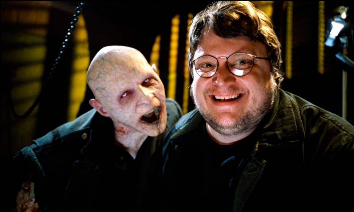 """Guillermo del Toro posing with a vampire from the TV show """"The Strain."""""""