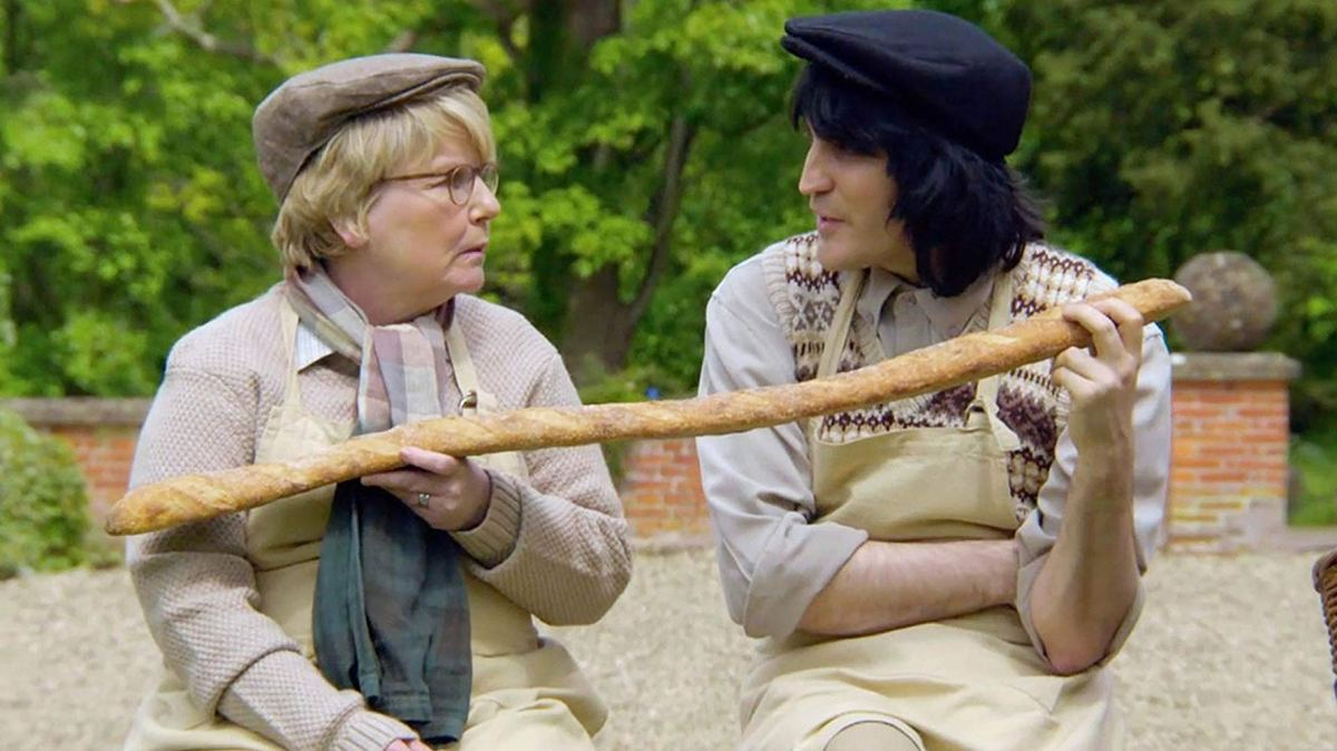Hosts Sandi and Noel are dressed up in vintage baking outfits, and hold a comically long bread stick.