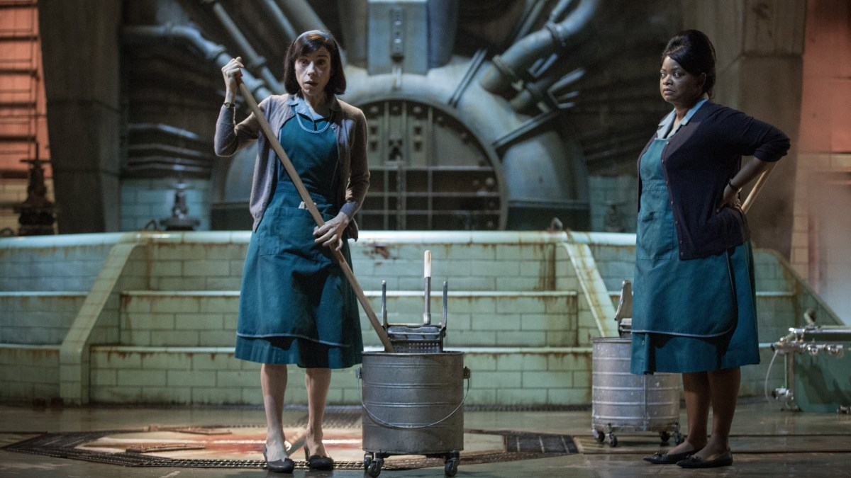 Eliza and her friend Zelda standing in from of the Amphibian Man's tank. The pyramid structure and pipes are shown in the background.
