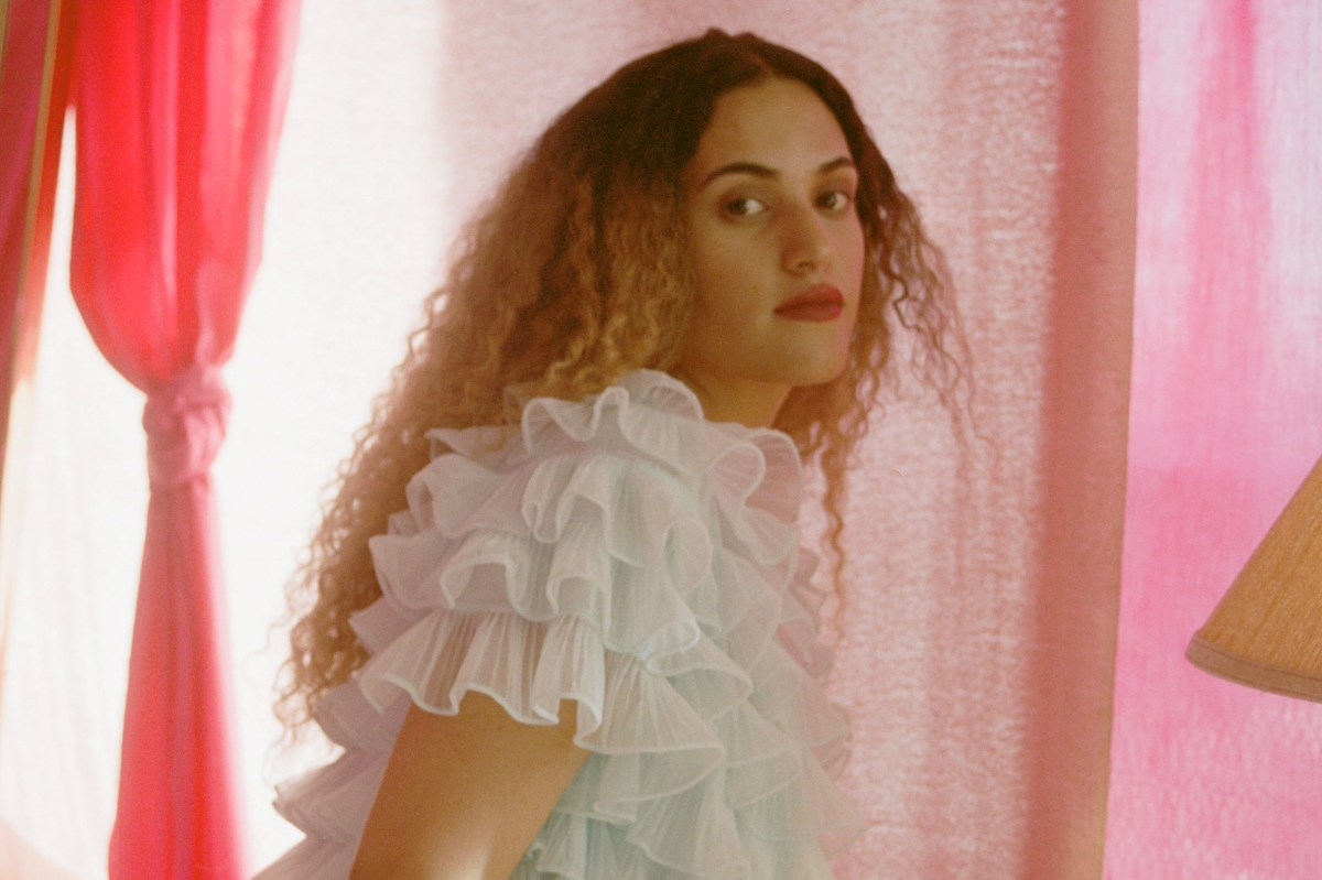 Empress Of in a pastel blue shirt standing in front a pink curtain in When I'm with him music video
