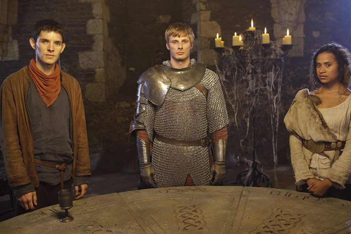 Arthur stands between Merlin and Gwen, showing the conflict between Merthur and the canon ship.