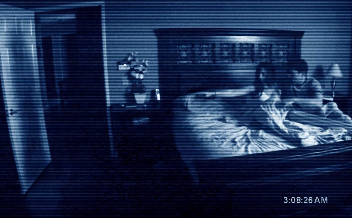 Katie and Micah from Paranormal Activity pointing at a shadow on their bedroom door