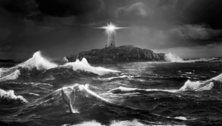 The lighthouse shining a light as waves crash violently around the island. A mermaid tail can be seen in the water.