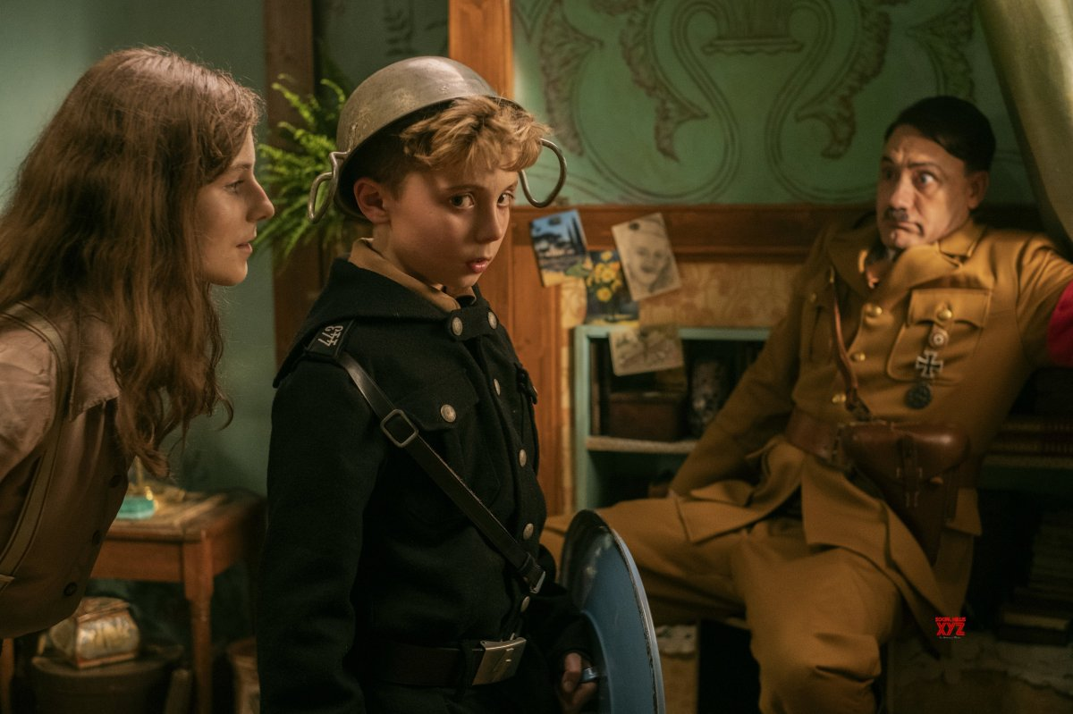 Elsa (Thomasin McKenzie) sneaks up behind Jojo (Roman Griffin Davis) as Adolph Hitler (Taika Waititi) looks on in horror.