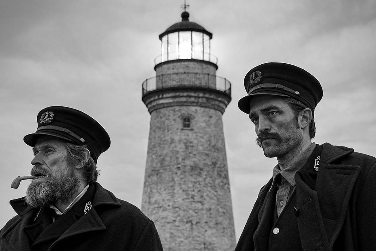 Robert Pattinson as Winslow (Prometheus) and Willem Dafoe as Wake (Proteus) stand in front of the foreboding lighthouse. Winslow is Prometheus and Wake is Proteus in Greek mythology.