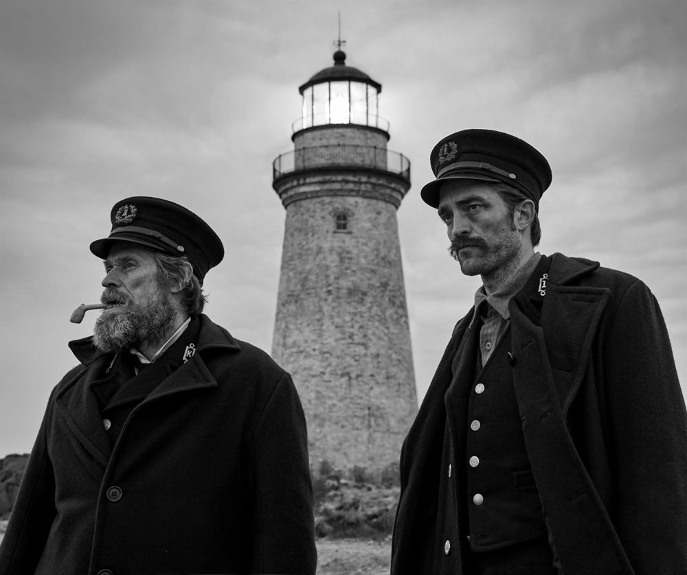 Willem Dafoe and Robert Pattinson as Wade and Winslow. They stand in front of the lighthouse their first day arriving to the island.
