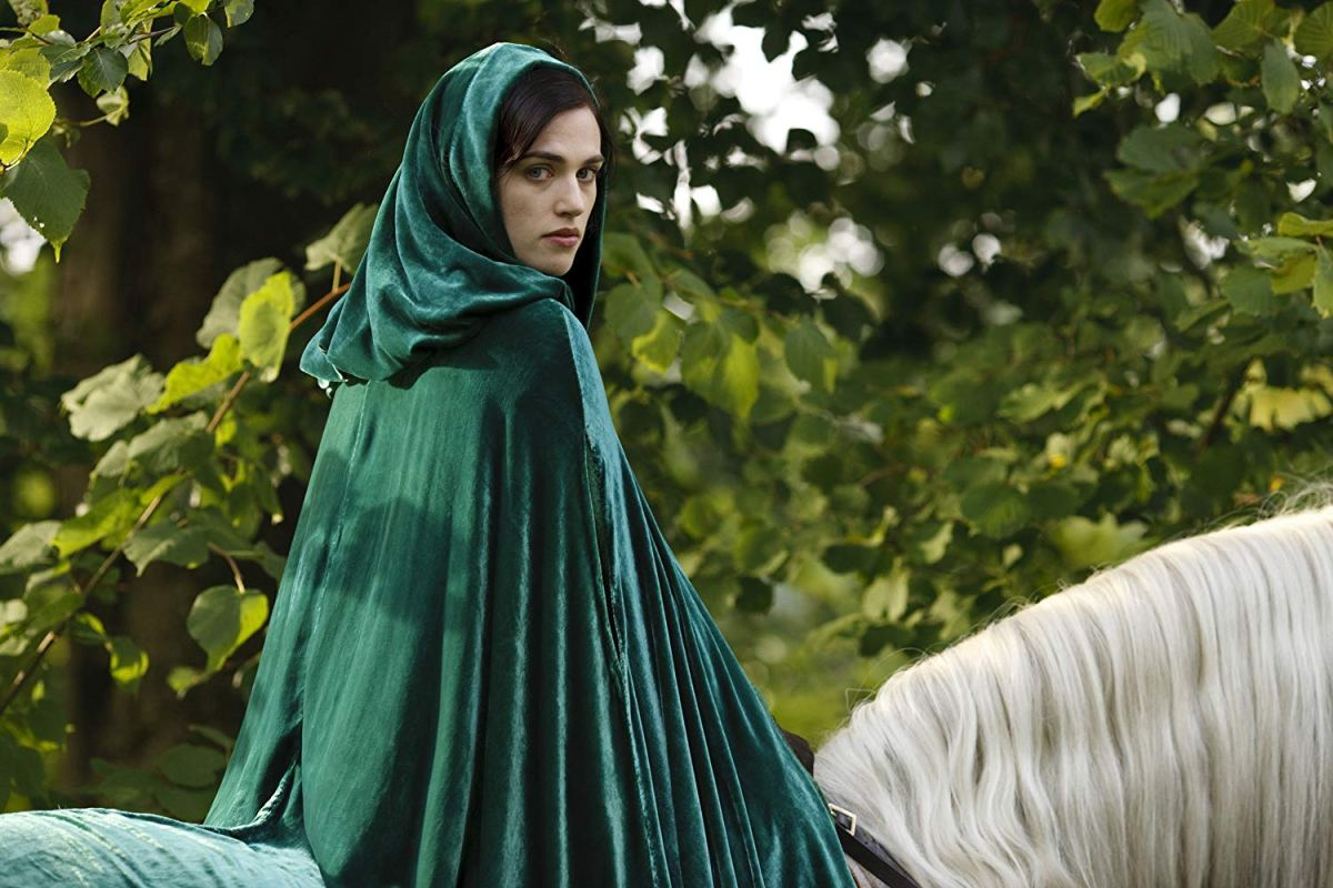 She wears a green cloak and rides a horse.