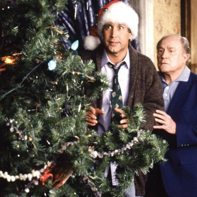 Clark and his father-in-law stand behind the Griswold Christmas tree.