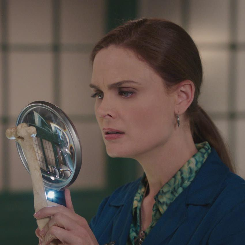 The main character analyzing a bone in a magnifying glass.