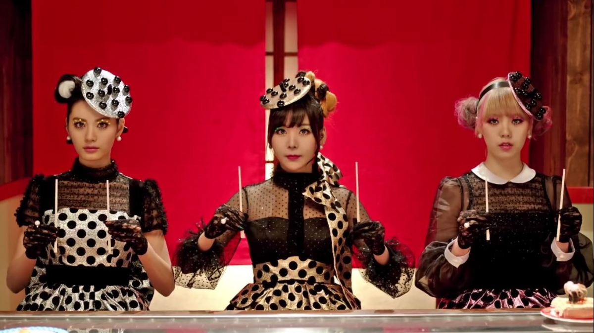 "Orange Caramel sits at a sushi bar and holds chopsticks in their K-pop music video, ""Catallena."""