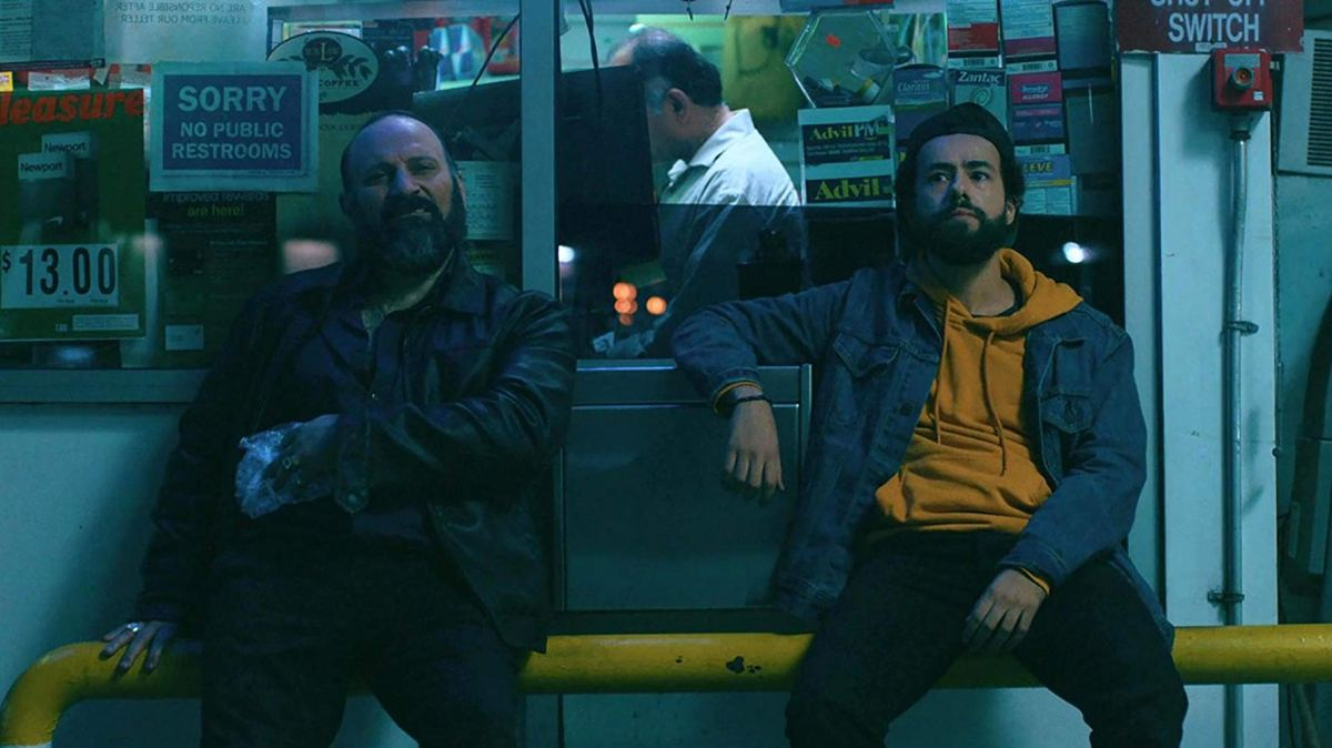 Ramy Youssef and co-star sitting outside a storefront in the 2019 TV show Ramy.