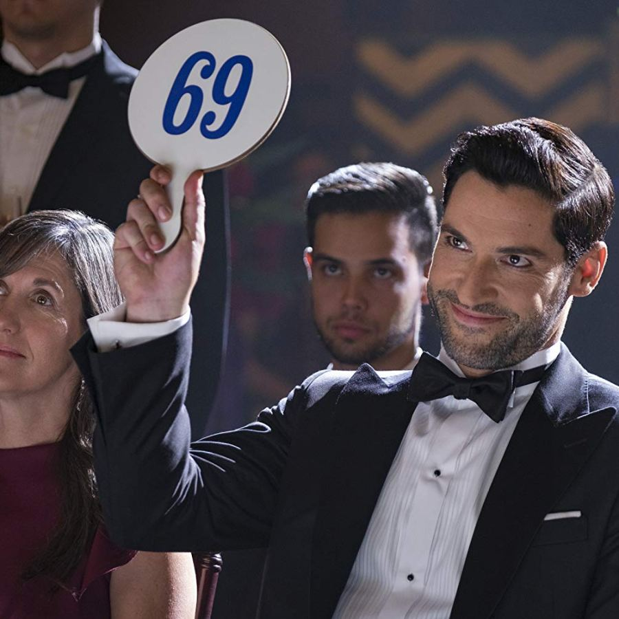 """Lucifer Morningstar holds up a """"69"""" sign at an auction"""